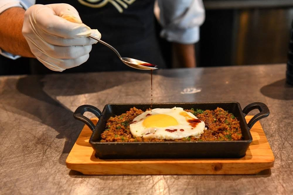 In this picture taken on July 16, 2021 a chef garnishes an egg over Keema - mince lamb meat with Kikkoman Soy Sauce at the Ishaara restaurant in Mumbai. AFP PHOTO